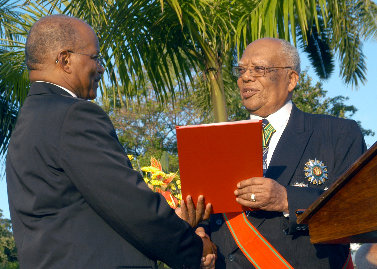 Former Governor-General, His Excellency the Most Hon. Sir Howard Cooke (right), presents the instruments of office to new Governor-General, His Excellency the Most Hon. Kenneth Hall.