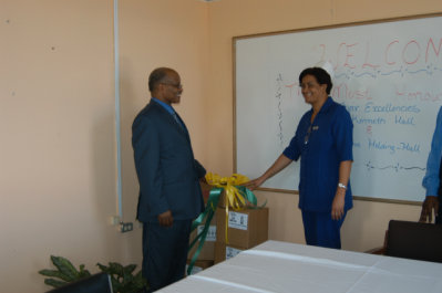 Governor General, His Excellency the Most Hon. Professor Kenneth Hall, hands over boxes of foodstuff along with cleaning and disinfecting products to Director of Nursing Services at the Noel Holmes Hospital in Lucea, Denise Malcolm. The presentation, which is on behalf of Lascelles Chin, Chairman and Chief Executive Officer of Lasco Group of Companies, was made at the hospital.