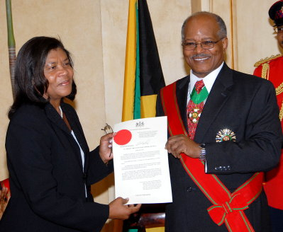 Chief Justice Zaila McCalla (left), shows her instrument of appointment as Head of Jamaica's Judiciary, shortly after Governor General His Excellency the Most Honourable Professor Kenneth Hall (right), presented it to her at the official swearing ceremony, held at King's House on June 26.