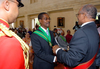 Governor General, His Excellency the Most Hon. Professor Kenneth Hall (right), presents the instrument of appointment to President of the Court of Appeal, Justice Seymour Panton, at the official swearing-in ceremony held on July 6 at King's House.