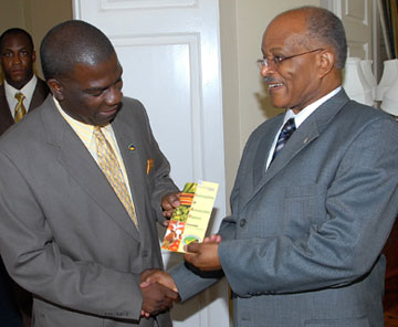 Governor-General, His Excellency the Most Hon. Professor Sir Kenneth Hall (right), accepts a brochure containing information about the Certification of Agricultural Produce Programme from Senator Norman Grant, President of the Jamaica Agricultural Society (JAS), during a call on the Governor-General on October 15, at King's House.