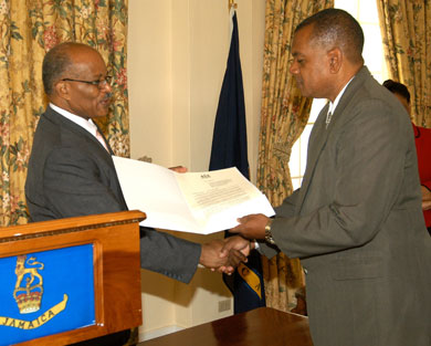 Governor General, His Excellency, the Most Hon. Professor Sir Kenneth Hall, (left) presents a copy of the Proclamation declaring November as Drug Awareness Month, which he read during a brief ceremony at King's House on October 31, to Executive Director of the National Council on Drug Abuse, (NCDA) Michael Tucker.