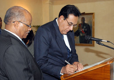 Governor General, His Excellency the Most Hon. Professor Sir Kenneth Hall (left), looks on as Justice Mahadev Dukharan, Judge of the Court of Appeal, signs document to confirm his status, at King's House on October 29. The Governor General presented three judges with their instruments of appointment to higher offices in the judiciary, during the ceremony.