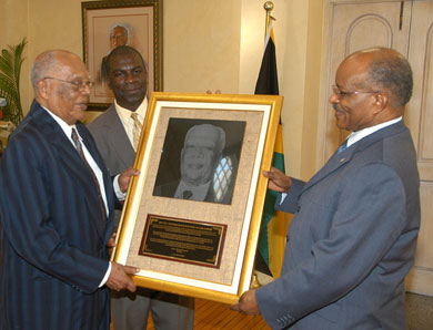 Governor-General, His Excellency the Most Hon. Professor Sir Kenneth Hall (right), presents the Jamaica Agricultural Society's (JAS) Gold Medal Award to his predecessor, the Most Hon. Sir Howard Cooke (left), at a ceremony, held at King's House on December 5. The award was presented to the former Governor-General in recognition of his outstanding contribution to nation building, particularly, in agriculture and the development of the JAS. At centre is JAS President, Senator Norman Grant.