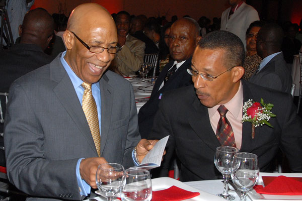 Governor-General, His Excellency the Most Hon. Dr. Patrick Allen (left), seems very amused at a comment made by President and Chief Executive Officer (CEO), Guardian Life Limited, Earl Moore, at the organisation's annual awards ceremony, held at the Jamaica Pegasus Hotel, in Kingston, on March 3. The Governor-General was the guest speaker at the function.