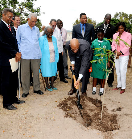 Governor-General, His Excellency the Most. Hon. Dr. Patrick Allen (centre), shovels dirt as he plants a Pious tree on the lawns of King's House, to launch the Jamaica Tree Growers Association's National Tree Growing programme, on April 22. Looking on (from left) are: Secretary, Jamaica Tree Growers Association, Guy Symes; Custos of Kingston, the Very Reverend Canon Weeville Gordon; Custos of St. Andrew, Bishop The Hon. Dr. Carmen Stewart; Student of St. Martin Primary School, Avrian Harris, and wife of the Governor- General, Her Excellency the Most Hon. Mrs. Allen.