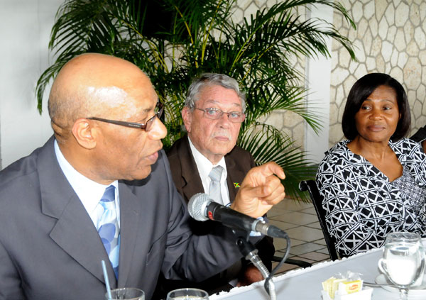 Governor General, His Excellency the Most Hon. Dr. Patrick Allen (left), addresses the audience at the Governor General's Achievement Awards youth consultative breakfast for the county of Middlesex held on May 15 at the Caymanas Golf and Country Club in St. Catherine. Listening intently are Custos for Clarendon, James deRoux (centre) and the Governor General's wife, Patricia Allen.