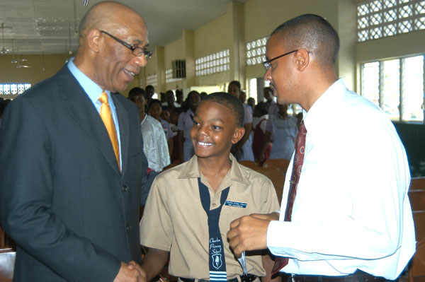 Governor-General, His Excellency the Most Hon. Sir Patrick Allen (L) greets student of Charlton Primary School in Alexandria, St. Ann, Karl Brown (C), while Karl Brown Sr., who is a Guidance Counsellor at the Brown's Town High School, shares the moment. His Excellency visited St. Ann yesterday (June 24), which was his first stop on his island-wide tour.