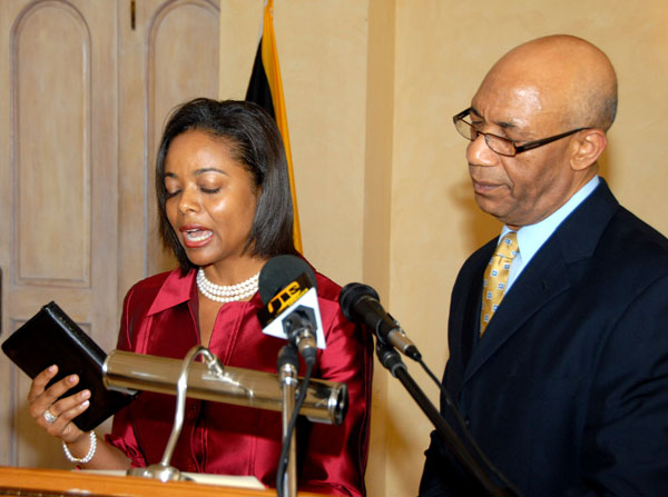 Governor-General, His Excellency the Most Hon. Sir Patrick Allen (right) looks on as Mrs Marlene Malahoo Forte takes the Oath of Allegiance and Oath of Office as a Senator, and Minister of State in the Ministry of Foreign Affairs and Foreign Trade, during a ceremony held at King's House on Wednesday (July 15).