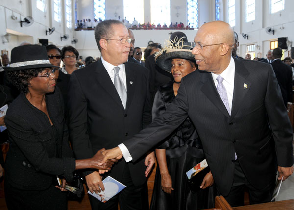 The Governor-General, His Excellency the Most Hon. Sir Patrick Allen reaches across to greet the wife of the Prime Minister, the Hon. Bruce Golding, Mrs. Lorna Golding, at the start of today's (August 8) funeral service for the late Lady Bustamante at the Sts. Peter and Paul Roman Catholic Church, Kingston. Looking on are: Mr. Golding(second left); and the wife of the Governor-General, Lady Patricia Allen(second right).
