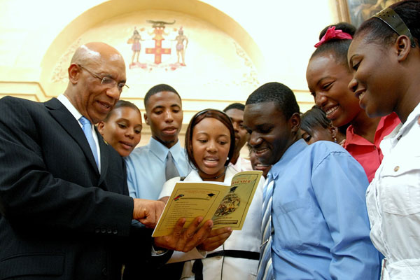 Governor-General, His Excellency the Most Hon. Sir Patrick Allen (left), goes through a Students' Motivational Manual with students from various institutions, who attended the ceremony to launch the manual, at King's House, on August 17.