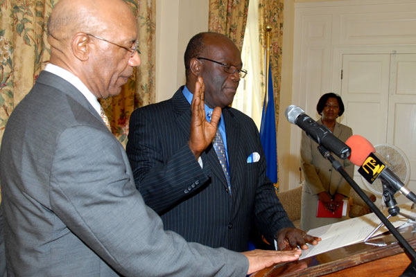 Governor-General, His Excellency the Most Hon. Sir Patrick Allen (left), looks on as Bishop Herro Blair takes the Oath of Office and Oath of Allegiance as Political Ombudsman for another five years, during a re-appointment ceremony, held at King's House, today (August 25. At right is the Governor-General's Secretary, Dionne Tracey Daniels.