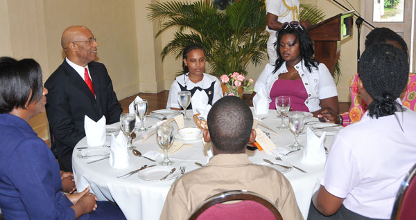 Governor-General, His Excellency the Most Hon. Sir Patrick Allen (2nd left), interacts with students, teachers, and community members of Tower Hill in Kingston, at a special luncheon held at King's House on September ,1 to honour students of the community, who excelled in the recent Grade Six Achievement Test (GSAT).