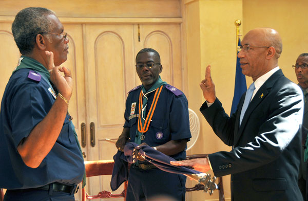 Governor-General, His Excellency the Most Hon. Sir Patrick Allen (right), says the scout's promise, as directed by Chief Commissioner of the Scout Association of Jamaica, Rev. Barrington Soares (left), during a ceremony at King's House, today (September 4), to invest the Governor-General as Chief Scout of Jamaica. Also participating is the Association's Field Commissioner, Delroy Davis.