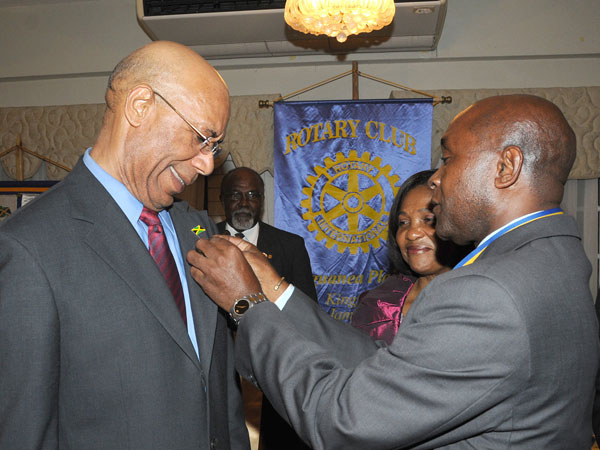 Governor-General, His Excellency the Most Hon. Sir Patrick Allen (left), seems very pleased as President of the Rotary Club of Liguanea Plains, Mrs. Astley Jones, affixes the Rotary Club pin to the Governor-General's lapel. Occasion was a Club meeting, held at Eden Gardens, in Kingston, on September. 10, at which the Governor-General was inducted as an Honorary Rotarian. Looking on (partially hidden) is the Governor-General's wife, Lady Allen.