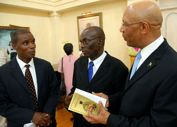 Governor-General, His Excellency the Most Hon. Sir Patrick Allen (right), discusses the contents of the Students' Motivational Manual with its author, Archibald Edwards (centre) and Publishing Director at the West Jamaica Conference of Seventh Day Adventists, Pastor Rohan Sewell , at the official launch of the handbook, at King's House, on August 17.