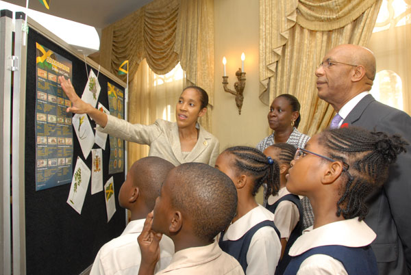 The Governor-General, His Excellency the Most Hon Sir Patrick Allen, listens as Chief Executive Officer (CEO) of the Jamaica Information Service (JIS), Mrs. Donna-Marie Rowe (far left) explains a poster depicting Jamaican Dollars and Cents for the benefit of students of Vaz Preparatory School, Kingston, who were on a tour of King's House while the JIS staged an exhibition there as part of its Heritage Week activities. Also in the picture is Grade 4 Supervisor at Vaz Prep, Mrs. Suzette Bennett (centre). The tour took place Wednesday (October 14).
