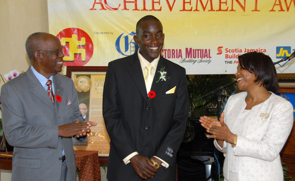 Mr. Nicholas Powell, graduate of the University of Technology (UTech), and a recipient of the Governor General's National Youth Award of Excellence for 2009 (centre), is applauded by Her Excellency the Most Hon. Lady Allen, wife of the Governor-General and Custos of Manchester, Hon. Dr. Gilbert Allen, at the presentation ceremony, which took place at King's House on November 11.