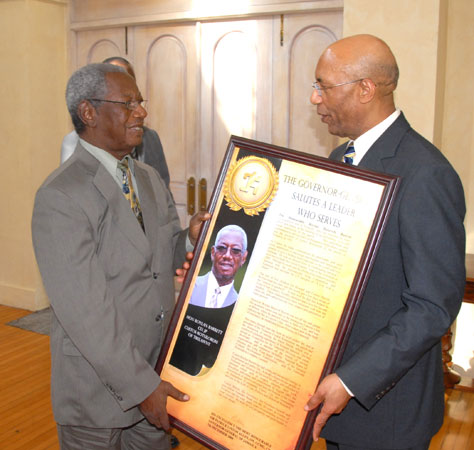 The Governor-General, His Excellency the Most Hon. Sir Patrick Allen (right), presenting outgoing Custos Rotulorum of Trelawny, the Hon. Roylan Barrett, with a citation in recognition of his18 years of service in that capacity, during an appreciation luncheon at King's House on Monday (December 7). The luncheon also honoured fellow Custodes, the Rev. Canon. Weeville Gordon, Kingston, and the Hon. Clarence Nelson, St. James, who have or will demit office this year.