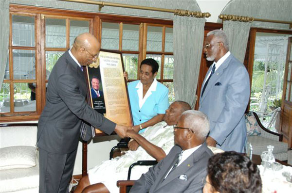Governor General, His Excellency the Most Hon. Sir Patrick Allen (left) presents a citation to retired Custos of St. James, Hon. Clarence Nelson (seated 3rd right), at his home in Anchovy St. James last week. Sharing the moment are Custos Nelson's wife Lucille Nelson (standing 2nd left); former Acting Custos Enel Brydson (standing 3rd left); Custos of St. James Hon. Ewen Corrodus (seated 2nd right) and wife Daphne Corrodus.