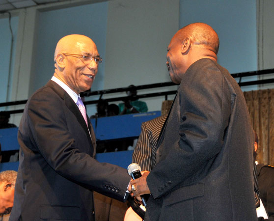 Governor-General, His Excellency, the Most Hon. Sir Patrick Allen (left) is greeted by founder of Power of Faith Ministries in Portmore, St. Catherine, Bishop Dr. Delford Davis, when he arrived for the Ministry's national prayer gathering held at the National Arena on Wednesday, January 6.