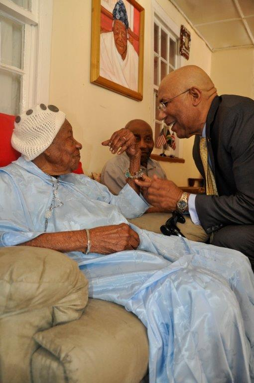 Governor-General Sir Patrick Allen share a ligh moment with Ms. Vioris Brown, the world's second oldest person alive at her Duanvale home in Trelwany on March 9, 2017. looking on is her son Mr. Fairweather.