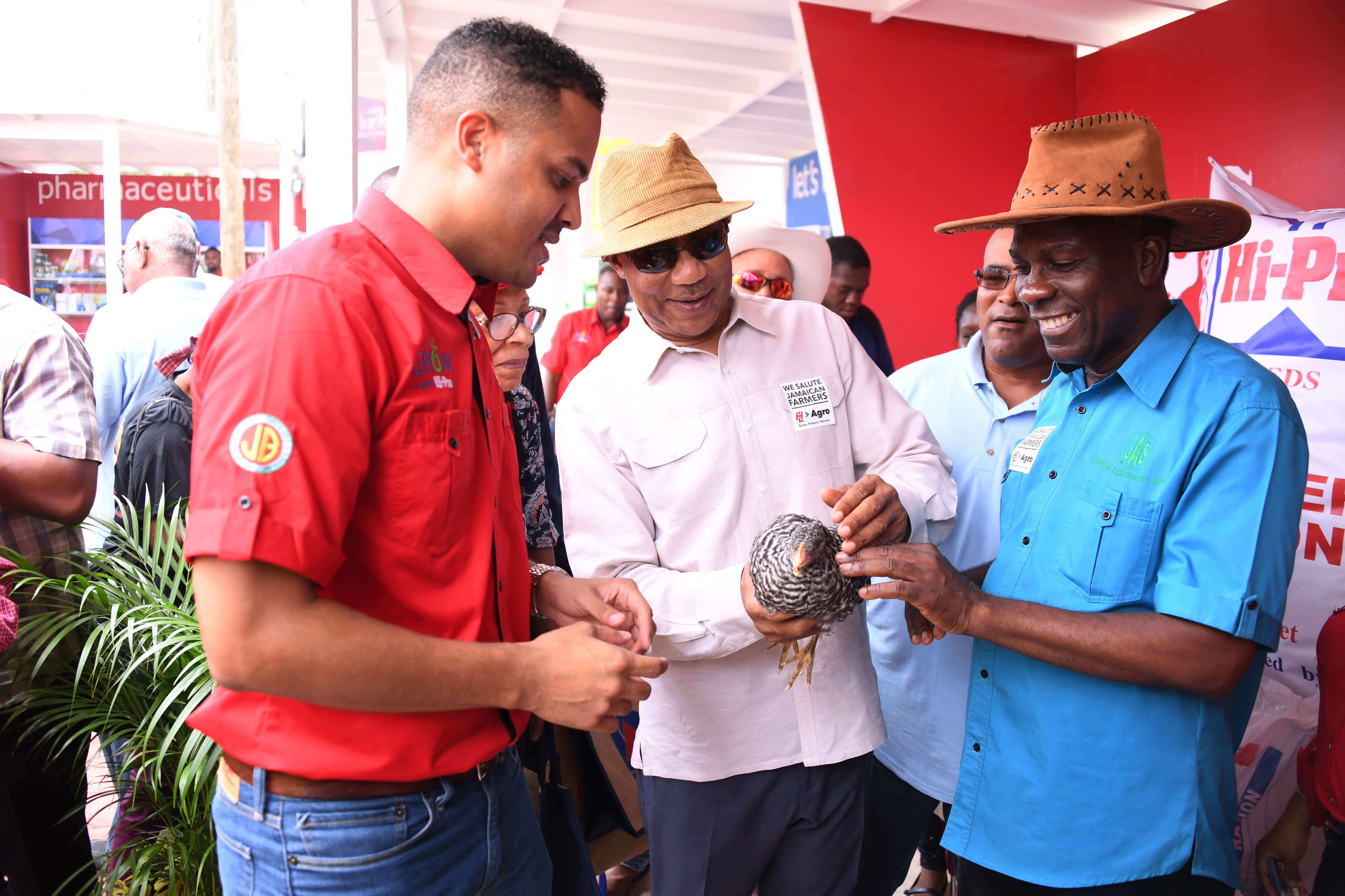 His Excellency Sir Patrick Allen (centre) holds a chicken during his tour of the Hi Pro booth at the Denbigh Agricultural, Industrial and Food Show in Clarendon on Sunday (August 6, 2017). Looking on are President of Jamaica Agricultural Society, Mr. Norman Grant (right) and a Hi Pro Feed Representative.