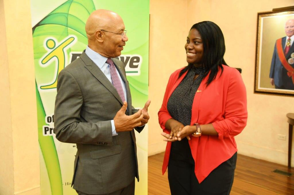 Sir Patrick Allen interacts with Dr. Angelica Baker, a scholarship recipient of the inaugural I Believe Initiative Summer Of Service Competition in 2013 during the awards ceremony yesterday (August 22, 2017).