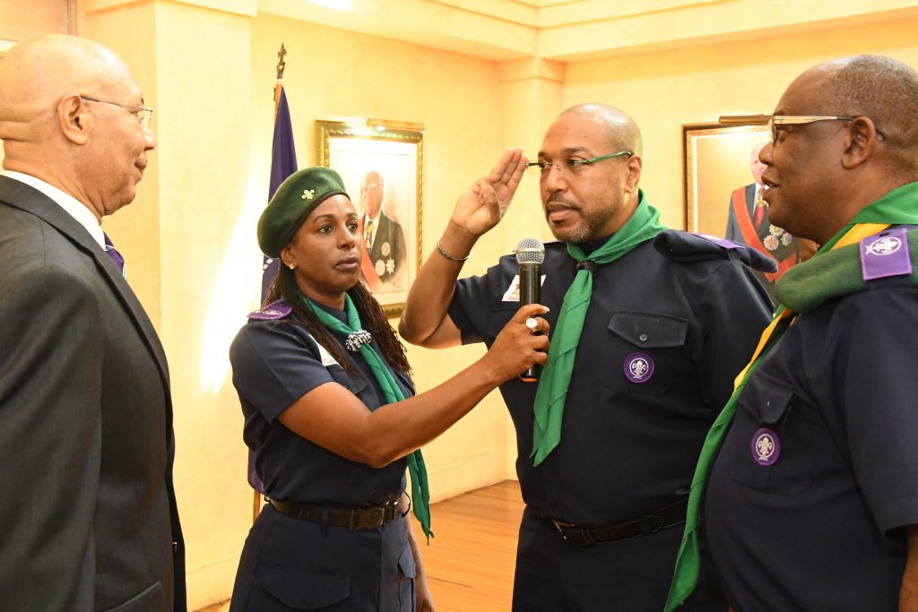 Governor-General Sir Patrick Allen and Chief Scout (left) receives a salute from new President of the Scout Association of Jamaica Mr. Richard Simpson (second right) at the Promise Renewal Investiture Ceremony held at King's House on Friday, October 6. Looking on (right) is Mr. Maurice Brown Chief Commissioner while Mrs. Karen Harriott Wilson (second left) assists with the proceedings.