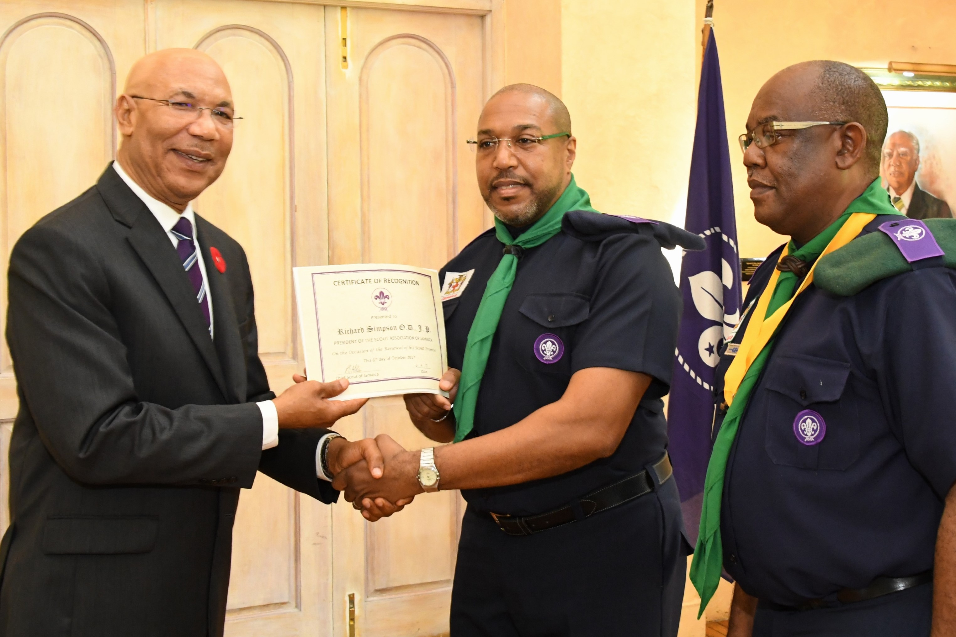 Governor-General Sir Patrick Allen (left) presents Mr. Richard Simpson with his certificate of appointment as the new President of the Scout Association of Jamaica.  Looking on is Mr. Maurice Brown Chief Commissioner.