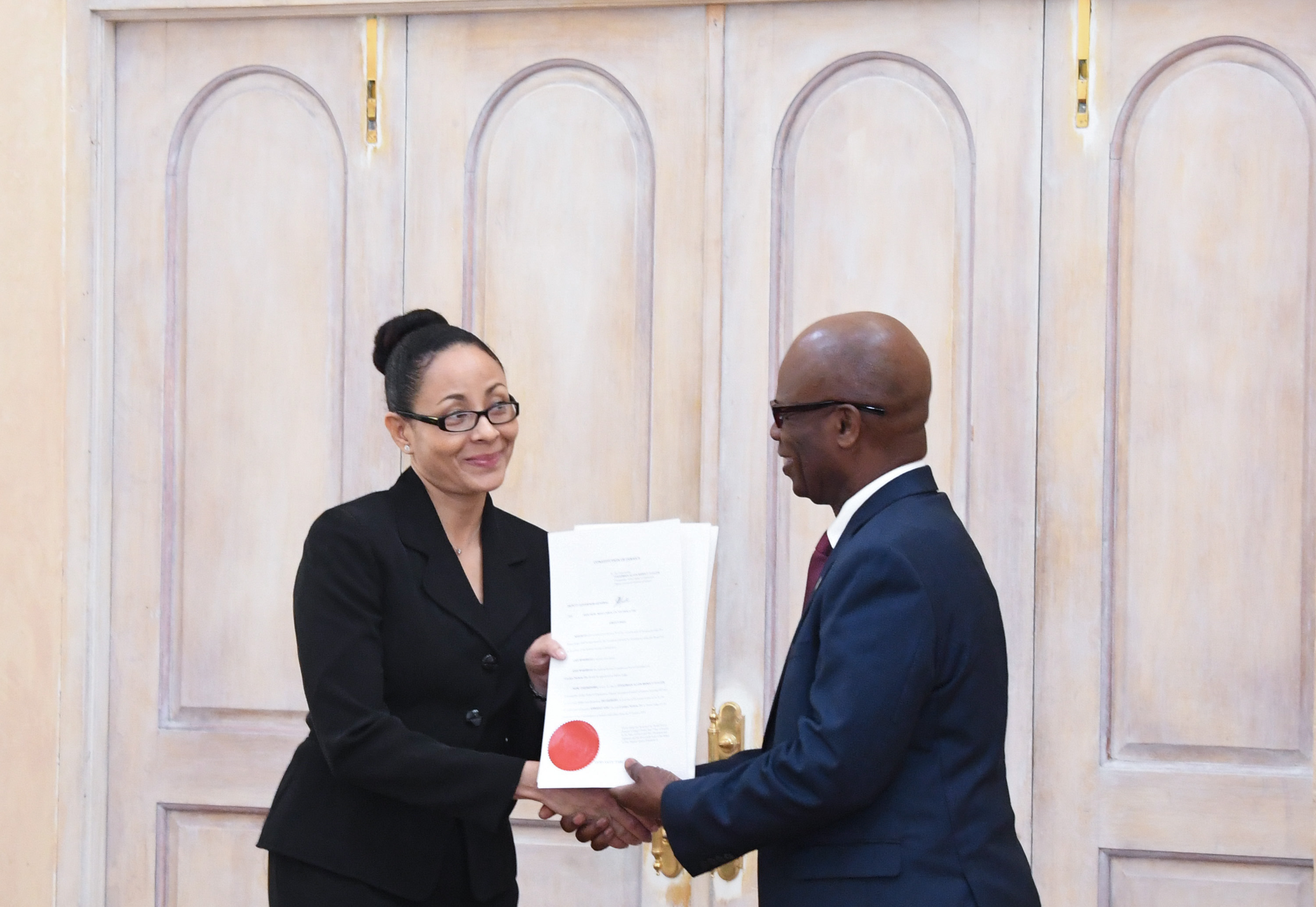 Deputy Governor-General the Honourable Steadman Fuller presents the Hon. Miss. Justice Carolyn N. Tie with her instrument of appointment.