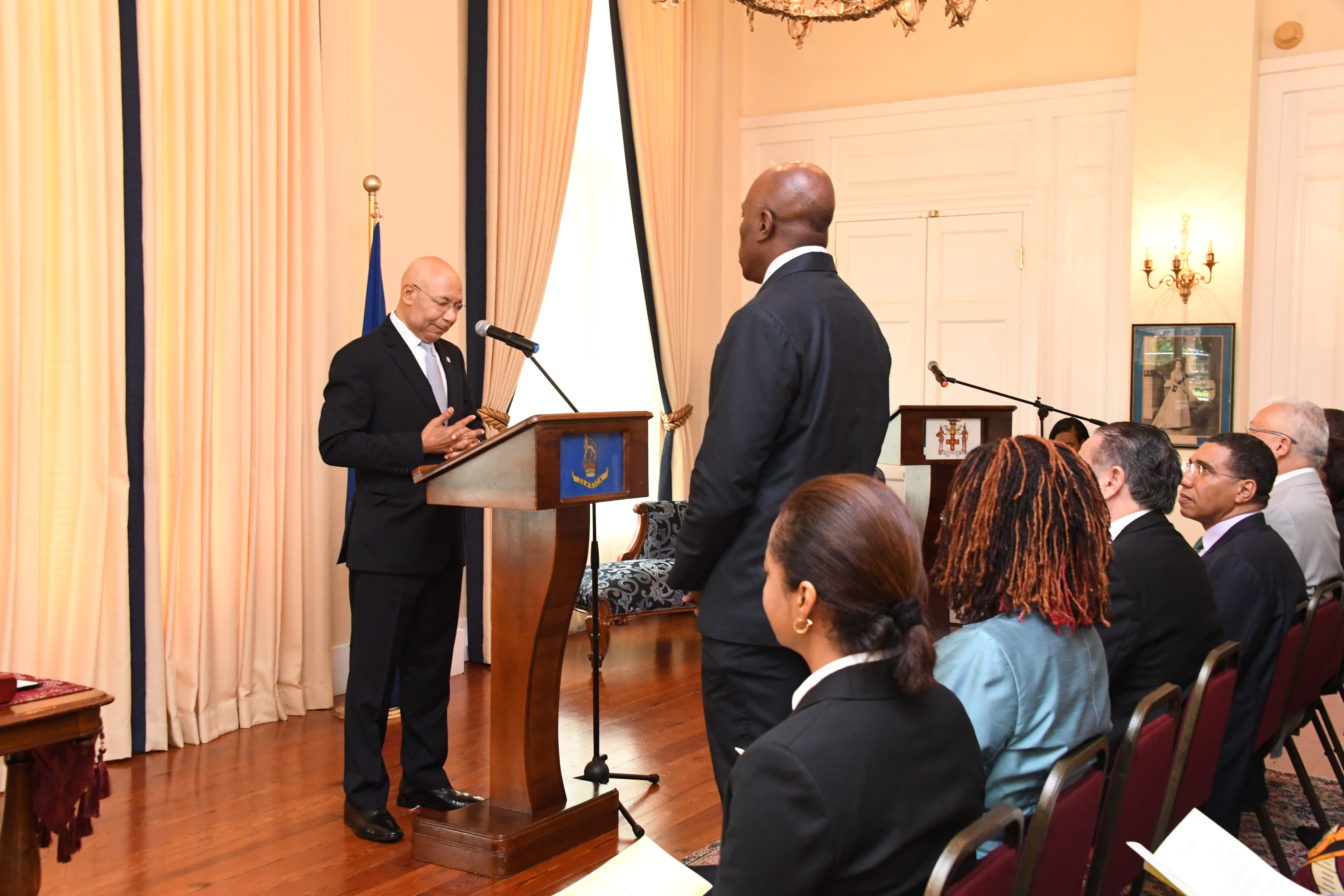 His Excellency The Governor-General reads the Instrument of Appointment for the Honourable Mr. Justice Bryan Sykes as Acting Chief Justice of Jamaica.